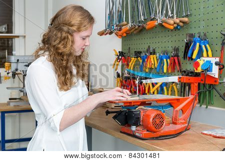 Caucasian teenage girl operating electric jigsaw