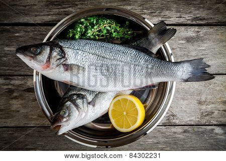 Two Raw Fresh Sea Bass In A Bowl With Thyme And Lemon