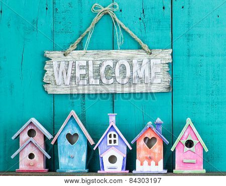 Welcome sign with bow by collection of birdhouses