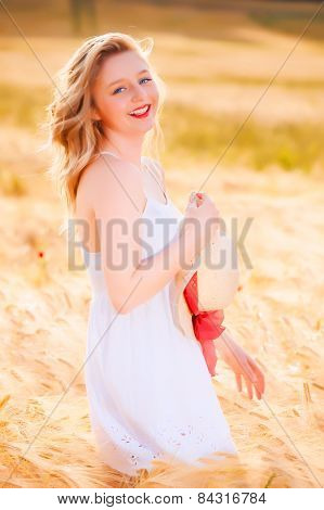 Happy Beautiful Young Blonde Girl In White Dress With Straw Hat Posing At Golden Wheat Field