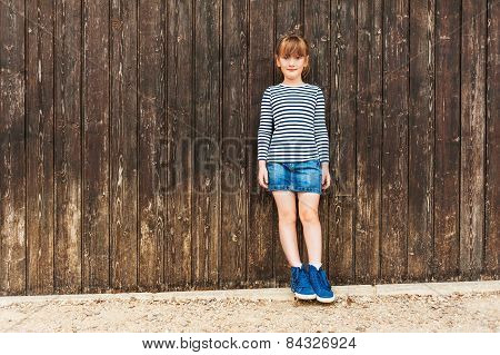 Outdoor portrait of a cute little girl, wearing frock, denim skirt and beautiful blue sneakers