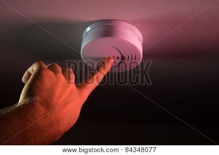 Person Hand Pressing Smoke Detector