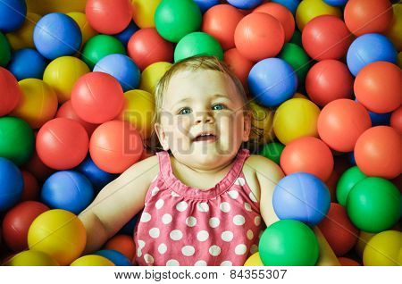 Little girl playing in plastic balls