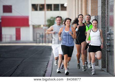 Grupo de amigos corre Downtown.