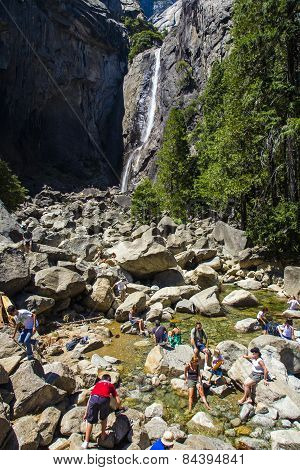 Tourists Cool Their Legs In The Lake Of The Lower Yosemite Waterfall