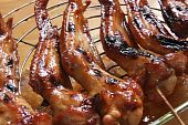 Grilled cooked chicken wings on wooden skewers poster