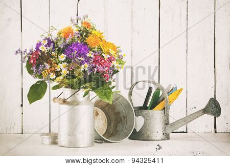 Flower bouquet in old milk churn, tin bucket and watering can. Vintage processing with dust and scratches.