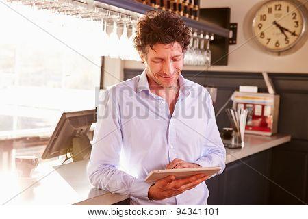 Male restaurant owner owner using digital tablet
