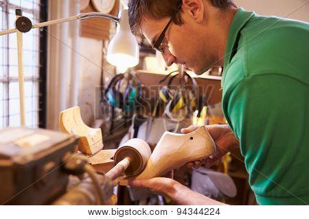 Shoemaker sanding shoe lasts in a workshop