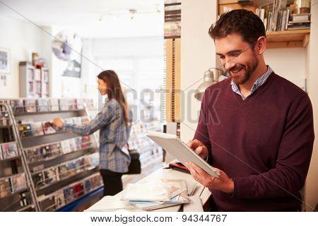 Man using digital tablet behind the counter at a record shop