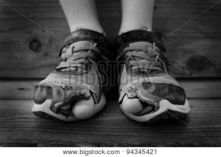 Black and white photo of shoes with holes in them and toes sticking out child kid young