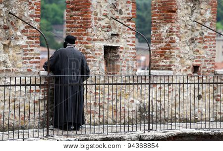 old priest dressed in black to look on the wall of the medieval castle