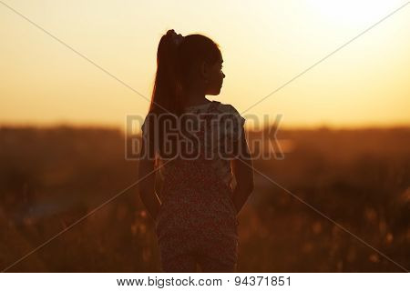 Girl standing in a field and looks into the distance poster