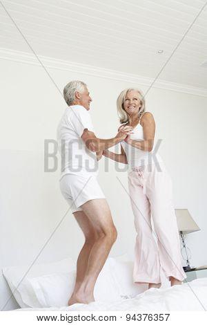 Senior Couple Jumping On Bed Wearing Pyjamas