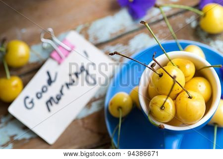 Blue Tea Cup Full With Yellow Cherries With Violets In A Pot