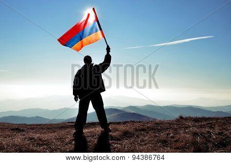 Man holding Armenian flag on a mountain peak