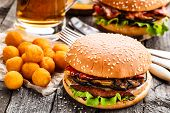 Delicious burgers with fried potato balls and beer on a rustic table poster