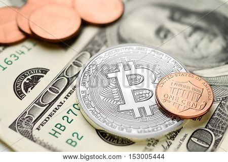 Bitcoin and one cent coins on US dollar bills. Electronic money exchange concept
