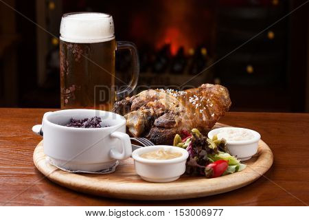 German cuisine - knuckle with garnish and a glass of bear on the table