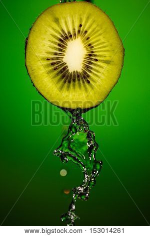 Ripe kiwifruit with drops of water isolated on green background