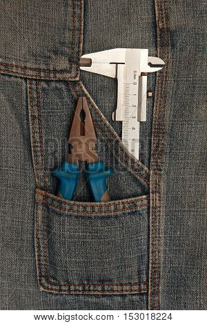 tools pliers and micrometer in jeans pocket
