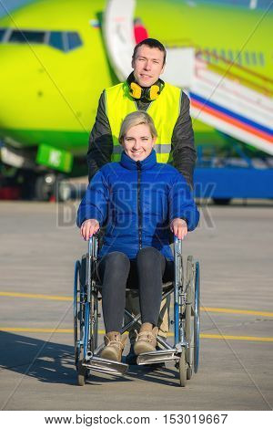 worker pushing the wheel chair with disabled person in the airport