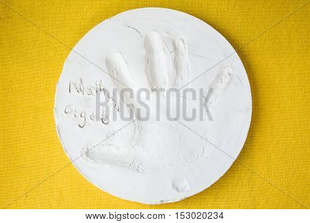 horizontal image of a round white clay plate with a small child's hand print pressed into it on a yellow background.