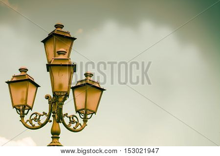 Antique streetlamp background with an intentional vintage effect applied and copy space.
