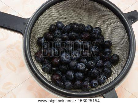 Freshly rinsed blueberries in strainer in white bowl