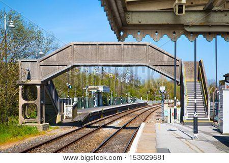RYE, UK - 1 MAY, 2016: Train statin, rails and foot bridge above the line