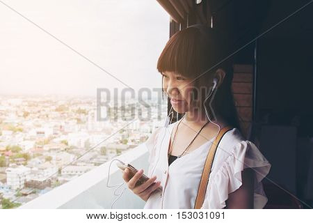 Asia girl teenage holding smart phone listen music. Selective focus and soft flare sunlight.
