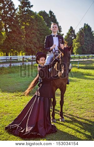 Multi ethnic Chinese and caucasian wealthy couple riding their horses on their estate