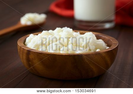 Milk kefir grains in wooden bowl with a glass of kefir in the back photographed with natural light (Selective Focus Focus one third into the kefir grains)