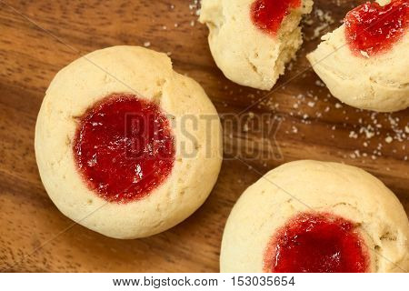 Thumbprint Christmas cookies filled with strawberry jam photographed overhead with natural light (Selective Focus Focus on the top of the cookies)
