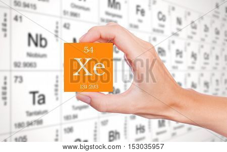 Xenon symbol handheld in front of the periodic table