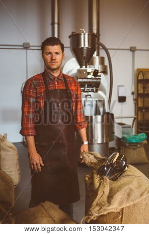 Portrait of handsome adult professional coffee roaster looking at camera beside bags with coffee beans