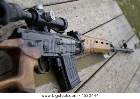 Rifle Gun Laying On Wooden Desk