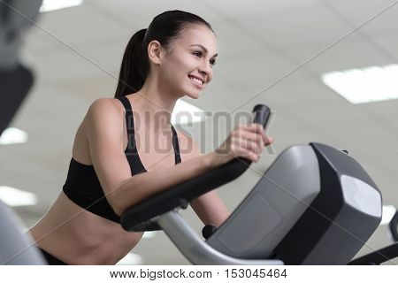 Keep yourself fit. Delighted young pretty girl training on a treadmill and smiling while having her workout in a gym.