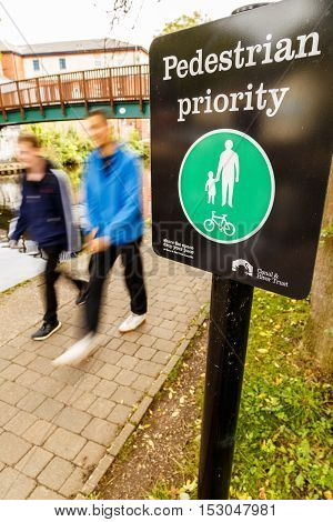 NOTTINGHAM ENGLAND - OCTOBER 19: Two young males walk past Pedestrian Priority sign alongside Nottingham canal. In Nottingham England. On 19th October 2016.
