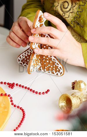 Woman assembling gingerbread cookies in the shape of Christmas tree. Close up view with selective focus.