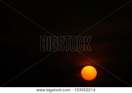 Dull sun giving off a faint orange & yellow glow in a dark morning sky.