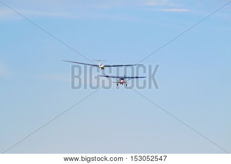 A sailplane in front of a blue sky glides through the air without its own motor drive.