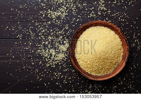 Raw couscous in bowl on dark wooden background from above. Flat lay style.
