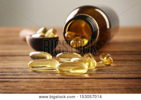 Cod liver oil capsules in spoon and glass bottle on wooden background