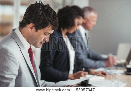 Diverse group of focused businesspeople working while sitting in a row together at a table in an office boardroom
