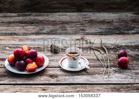 Cup of coffee and fresh plums on wood, free space. Warming drink with tasty fruit on old rustic wooden background, copy space for text