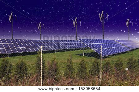 Solar panels with wind turbines against night sky