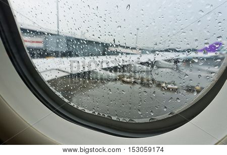 selective focus rain drop from window seat inside airplane with blurred wing background at plane park in airport before taking off