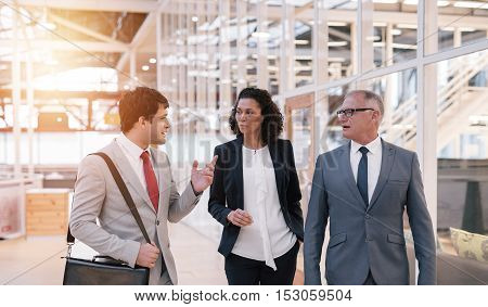 Dioverse group of businesspeople talking together while walking in the lobby of a modern office building