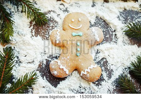 Gingerbread man making snow angel on flour in frame of pine-tree branches. Fun at kitchen, cooking art, Christmas treat preparing